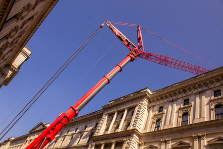 A huge red crane operates in the middle of an area of London city.