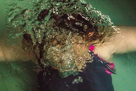 A person holds their breath whilst they go beneath the water.