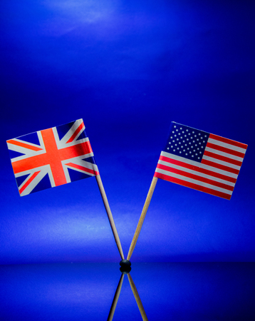 The American and British flags stand side by side against a sky blue background. Stock Photo