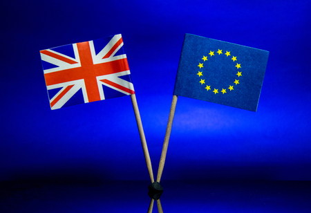 The British and EU flags stand together, against a sky blue background. Фото со стока