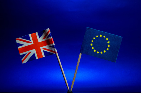 The British and EU flags stand together, against a sky blue background. 写真素材