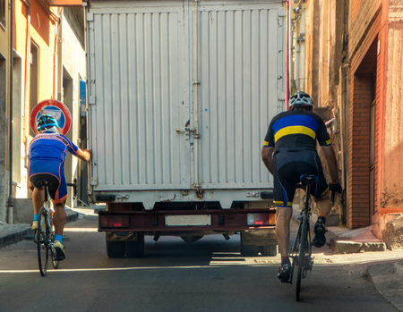 A cyclist chooses the easy / lazy option of holding onto the back of a truck to get up a hill.