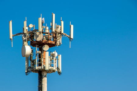 The top of a telecommunications tower against a plain blue, sky, background. Stok Fotoğraf