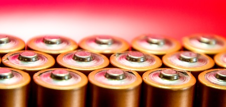 A collection of pencil AA batteries, taken close up at their heads.