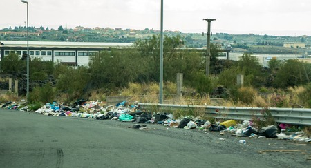A large collection of rubbish that has been dumped at the side of a busy road.