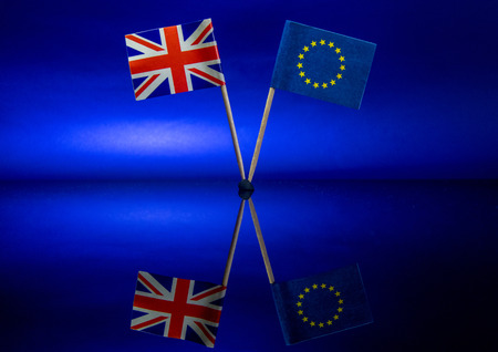 The British and EU flags stand together, against a sky blue background. Stockfoto