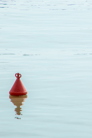 A small buoy sits in calm waters of a harbor area.