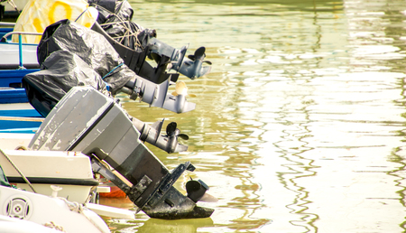 A row of outboard motors lifted out of the water. Banco de Imagens