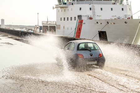 The driver of a small car takes a risk by driving full speed through a huge puddle.
