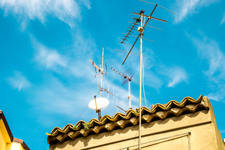 A typical Italian rooftop covered in antennas, against a blue sky. Stok Fotoğraf