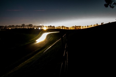 A rally undertaken on a racetrack, carried out at night  dusk.