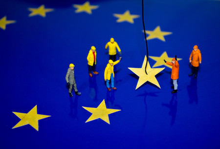 A team of construction workers work to remove a yellow star from the EU flag, representing Brexit. Stok Fotoğraf