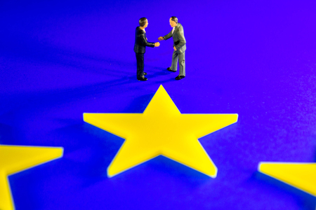 A meeting to discuss the Brexit issues.  Businessmen shown closeup on a EU flag. Stock Photo