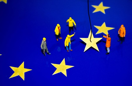 A team of construction workers work to remove a yellow star from the EU flag, representing Brexit. Stock Photo