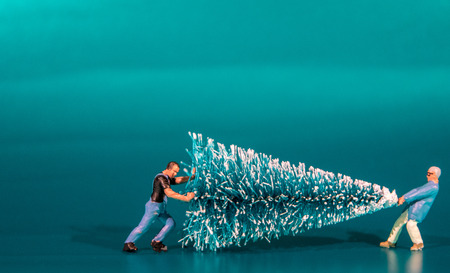 Una pequeña figura moviendo un árbol de Navidad. Foto de archivo