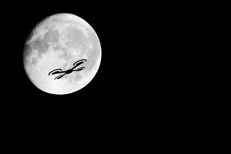 A night shot of a drone against the almost full moon. Showing the dangers of drones against other passenger occupied aviation.