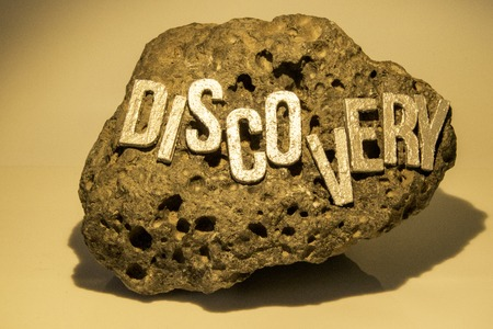The word Discovery on a rock surface to show the findings of any item really whether it be historic, treasure or for fun.