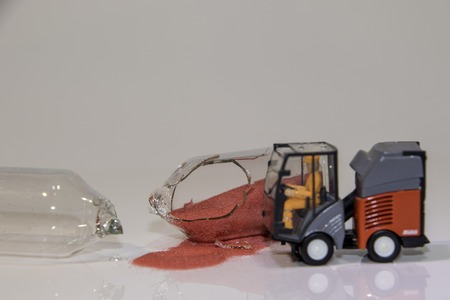 A glass egg timer is laying broken to show that the time is up ! A road sweeper has come along to clear up the mess. Reklamní fotografie