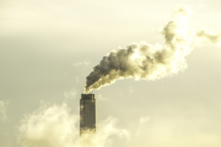 Steam  Smoke pours out the top of a chimney stack at a large power station. Stock Photo