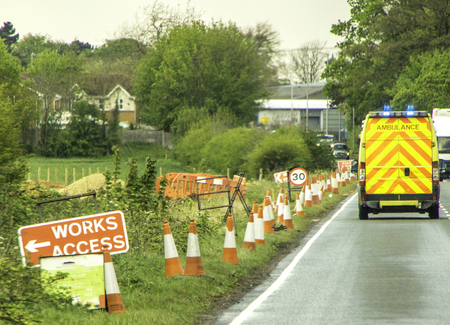 An Ambulance, in the United Kingdom, races down the road past roadwork cones in response to an emergency, on blue lights.