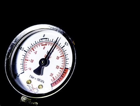 A closeup of a pressure gauge, shown in the dark.