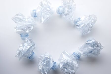 A collection of plastic bottles crushed and displayed on a white background. Imagens