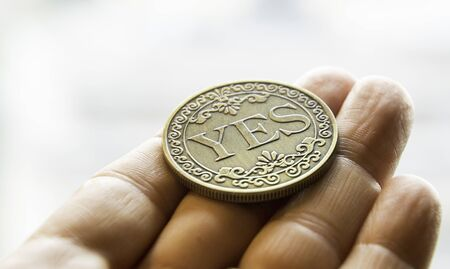 A large coin in a hand that has just been flipped shows the word Yes.