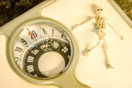 A tiny skeleton on a set of weighing scales.