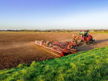 Wspaniały letni wieczór na płaskiej brytyjskiej wsi, na otwartych polach z trawą i zaoranej ziemi, gdy w tle zachodzi słońce.
