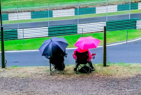 22nd September 2019 - Cadwell Racetrack, Lincolnshire, England. Two spectators on camp chairs, with umbrellas, brave the downpour of rain as all other spectators have gone home.