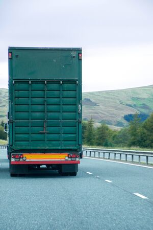 A lorry transporting goods of all sorts, traveling along a main UK motorway.