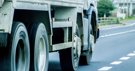 A closeup of wheels in motion from an articulated lorry, traveling along a UK motorway. Stock Photo