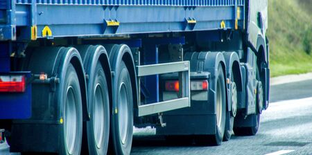 A closeup of wheels in motion from an articulated lorry, traveling along a UK motorway. Stock Photo - 131966784