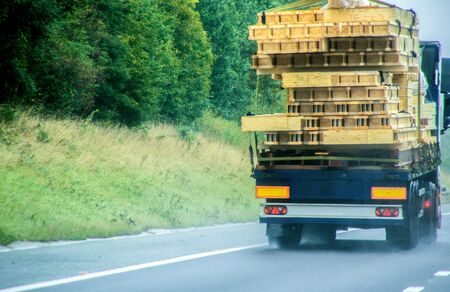 An articulated lorry carrying timber most likely for a new build property, traveling along a UK motorway. Stock Photo