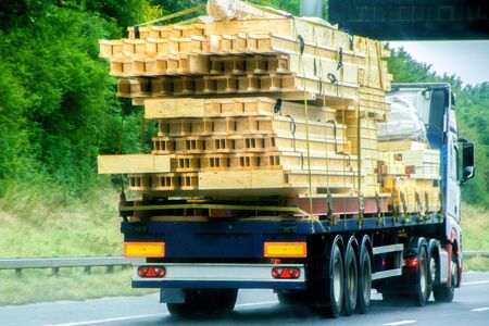 An articulated lorry carrying timber most likely for a new build property, traveling along a UK motorway. Stock Photo - 131968014