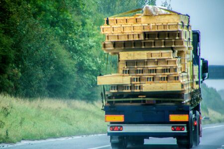 An articulated lorry carrying timber most likely for a new build property, traveling along a UK motorway. Stock Photo - 131968083