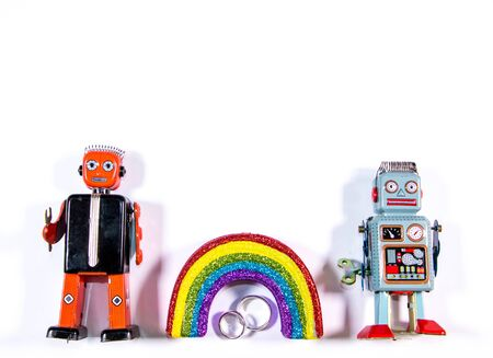 A LGBT relationship signified by two toy robots, wedding rings beside a colourful rainbow. Stock Photo
