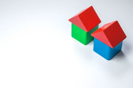 Two toy homes sit against a blank background that can be used for text. Stock Photo