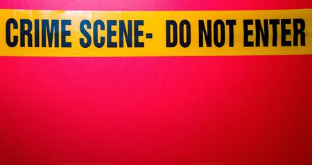 Crime Scene tape to secure and cordon off an area that has been involved in a crime of some sort, against a red background.