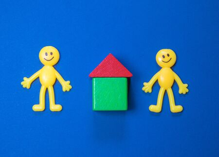 Yellow toy figure people stand by a wooden block house. The house possibly rented or a new investment. Stockfoto