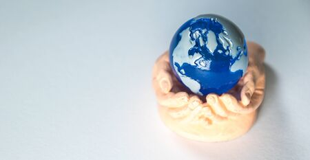 A cupped set of hands holds a miniature version of planet Earth. Reklamní fotografie