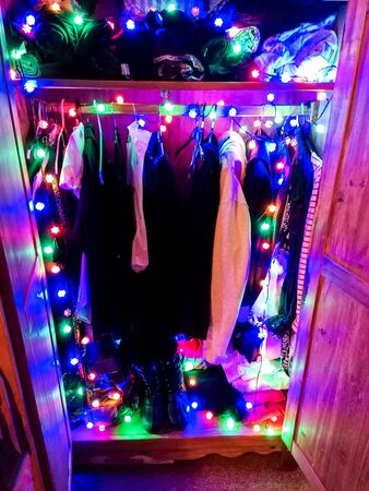 A series of Christmas lights, seen wrapped up within a cupboard full of clothes.