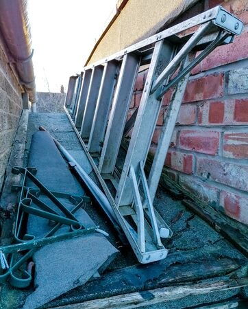 A set of common household ladders, stored away on top of a small sloping roof.