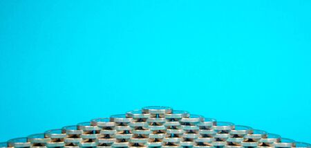 A stack of Pound Coins on a bright blue background. Stock Photo