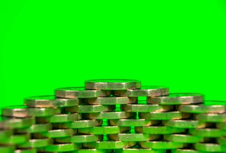 A pile of Pound Coins stacked against a green background.