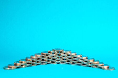 A stack of Pound Coins on a bright blue background.