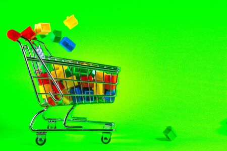 A supermarket trolley full of plastic houses. Taken against a solid green screen color. Stockfoto