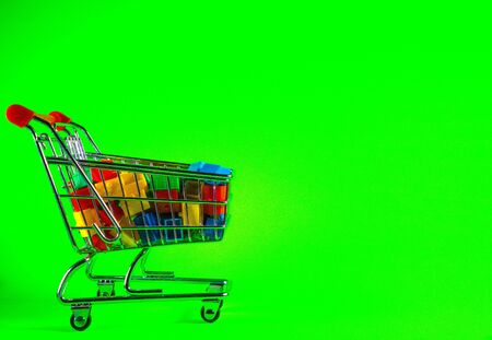A supermarket trolley full of plastic houses. Taken against a solid green screen color. Banque d'images