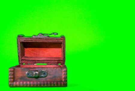A small toy wooden chest, taken against a bright green screen background.