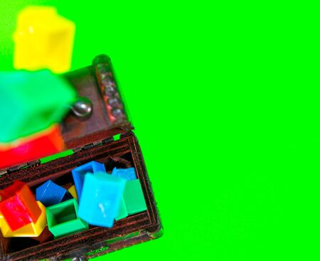 A wooden chest full of plastic houses, taken against a green screen background.